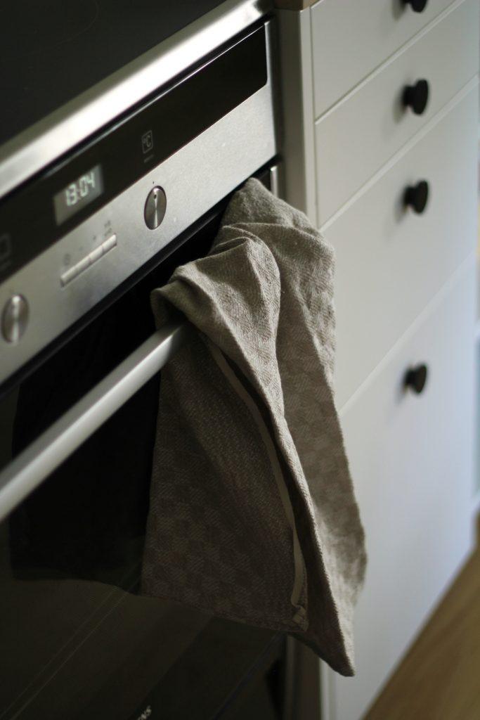 Moderni, graafinen keittiö ja käsityötekstiilit ovat oiva pari.