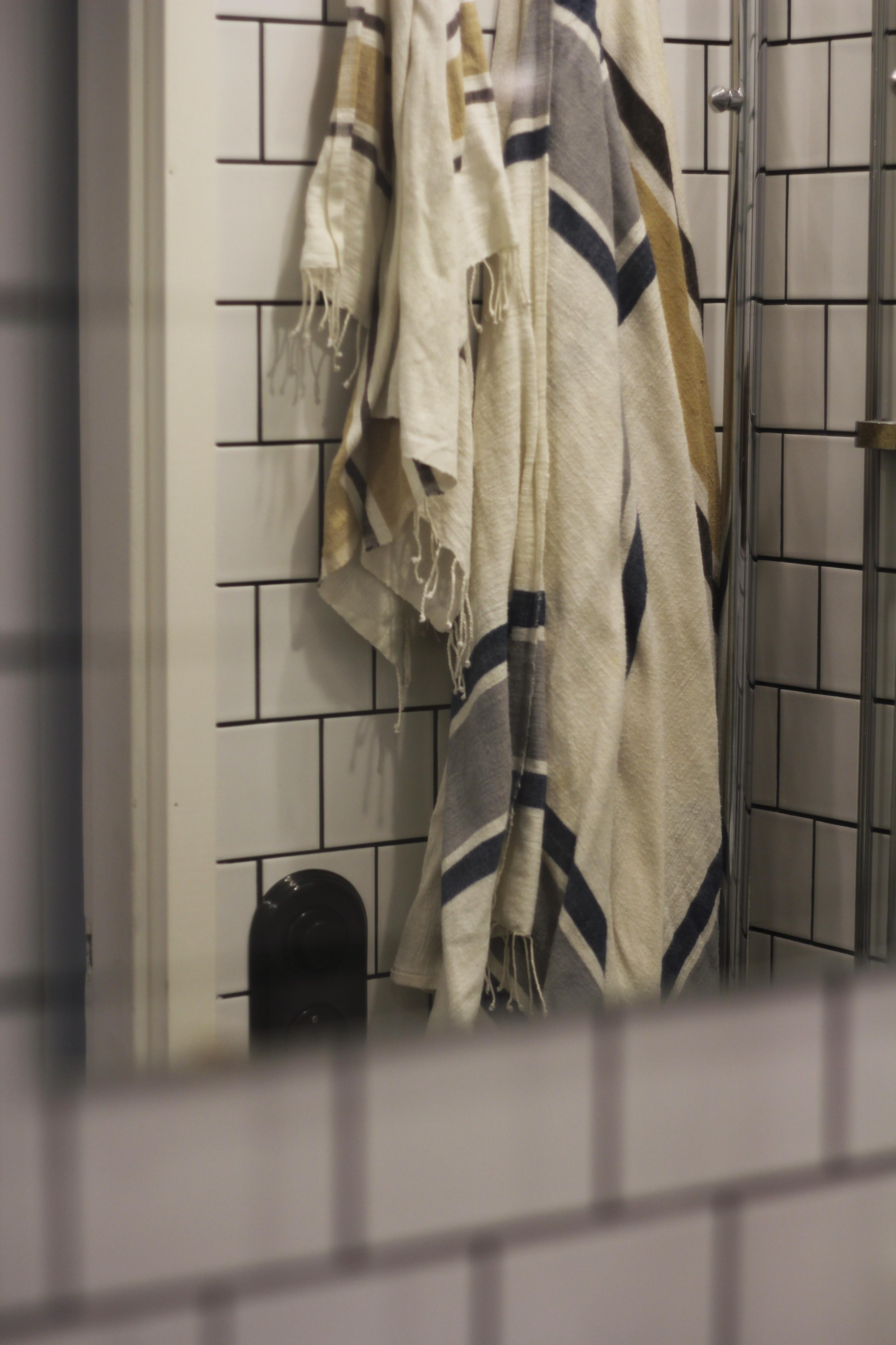 Pienessä kylpyhuoneessa jo kaksi kylpypyyhettä muodostaa aikamoisen keon. Vaihdoimme froteepyyhkeet kevyempiin ja vähemmän tilaa vieviin Hamam-pyyhkeisiin. Musta valokatkaisija valittiin sopimaan kaakeloinnin mustiin saumoihin.