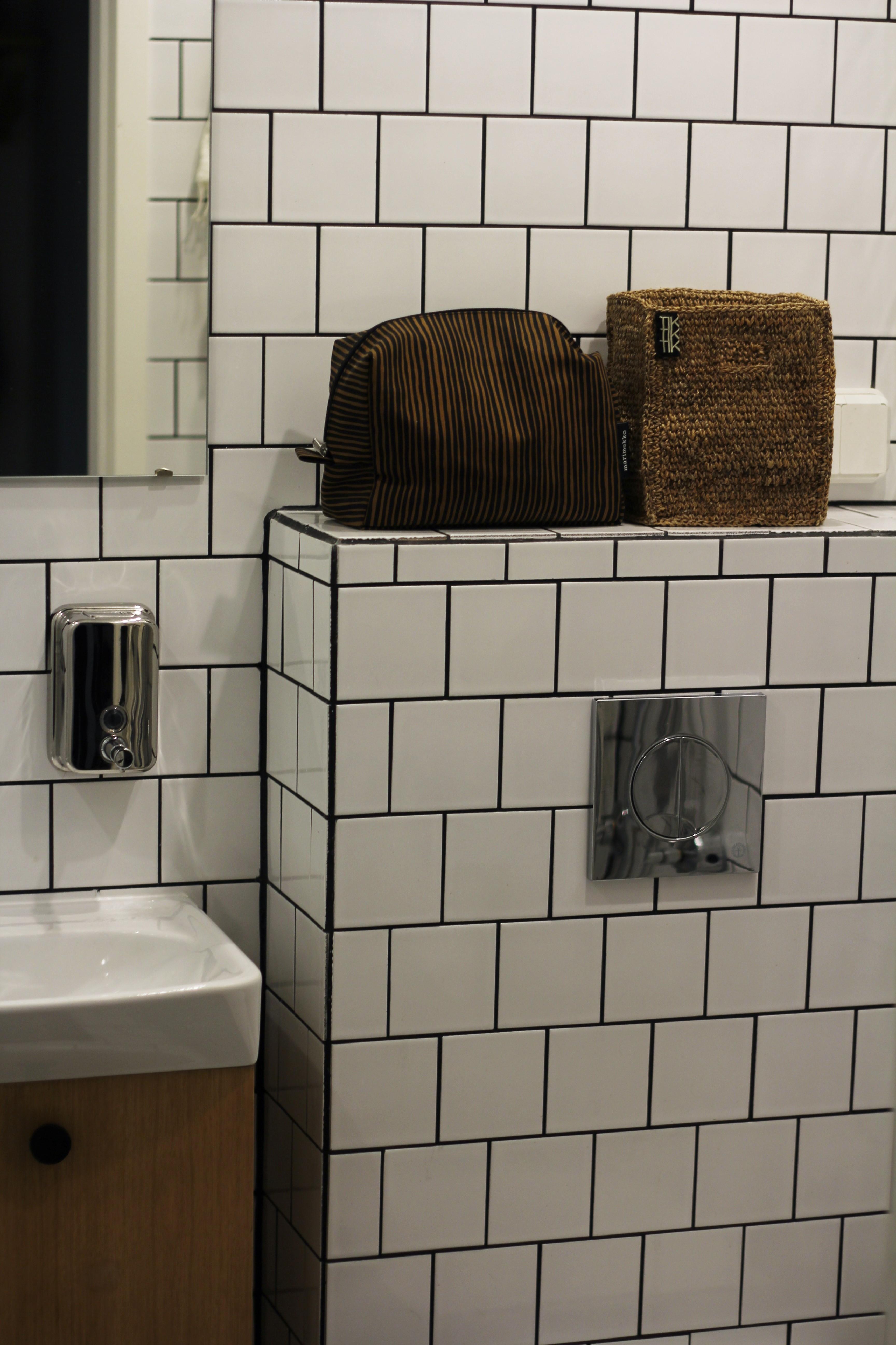 Seinä WC:n koteloinnin päälle on tulossa pari allaskaapille. Kaapin saapumiseen asti päivittäiset kosmetiikkatarvikkeet säilytetään Marimekon pussissa ja Tikaun korissa.
