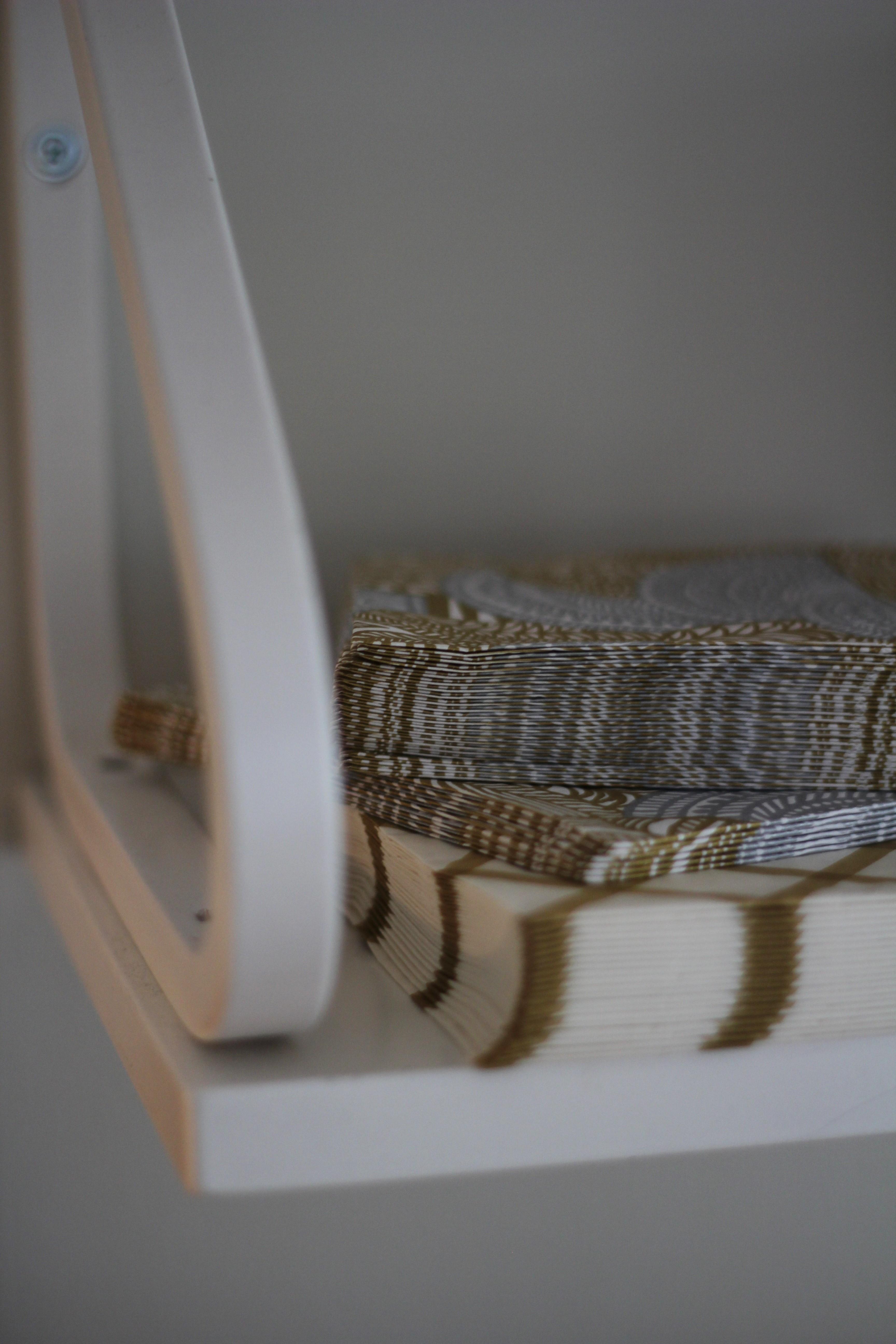 Käytän arkenakin kauniita servettejä, joita sopii kätevästi pino Artekin avohyllyn kulmalle.