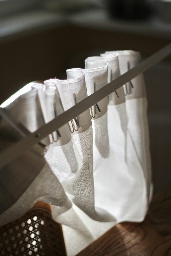 Sormikoukkuja käytettäessä verhot kannattaa mallata kiskossa ennen kiskon poraamista seinään. Valkoisessa pellavaverhossa yläreuna oli luonnonvärisiä verhoja korkeampi, joten kiskokin piti keittiössä asentaa alemmas kuin ruokailutilassa. Muuten verhot olisivat rytyssä kattoa vasten.